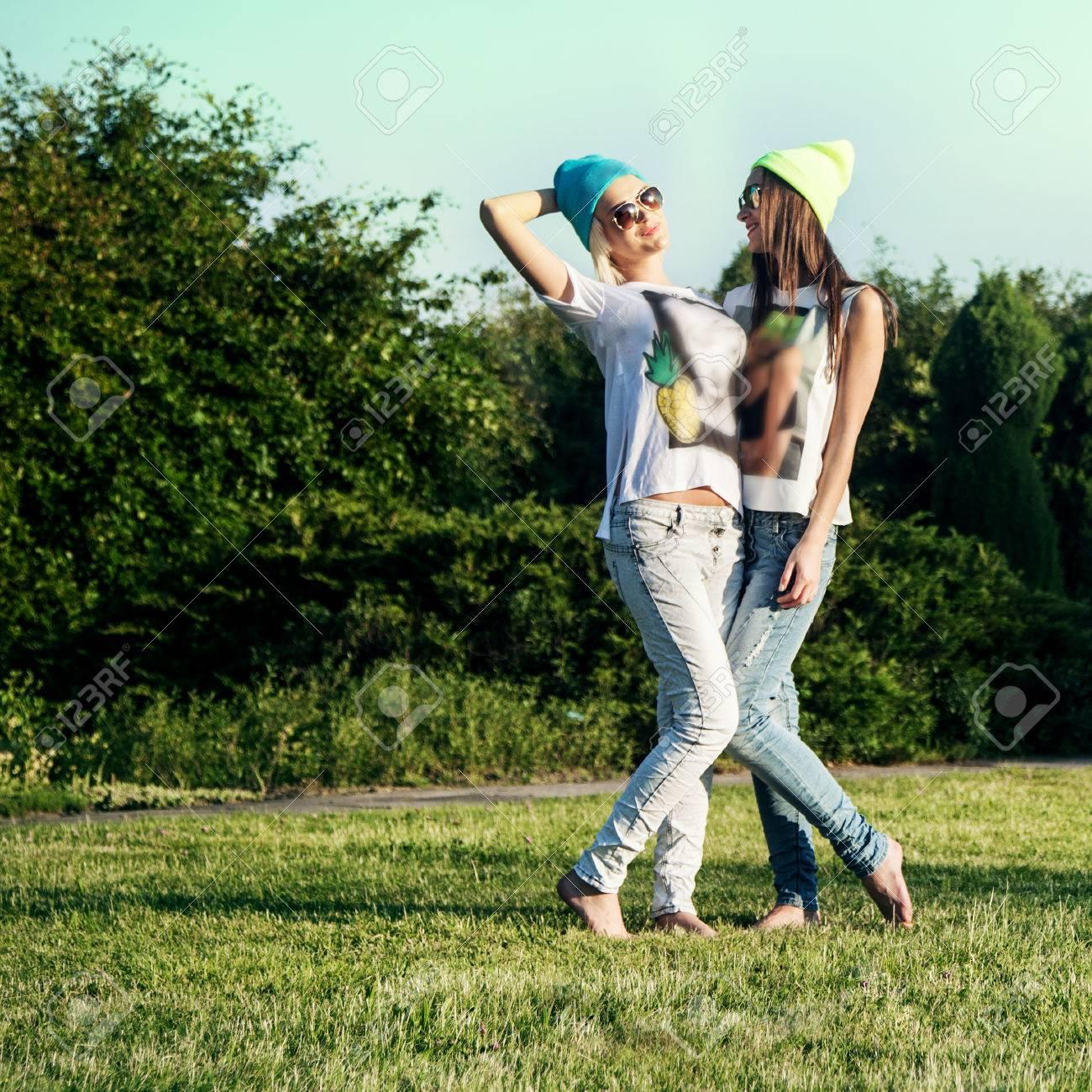1d8ba4a35995 Dos chicas hermosas jóvenes posando al aire libre en el parque, vistiendo  ropa de moda. Foto del verano. Mejores amigos.