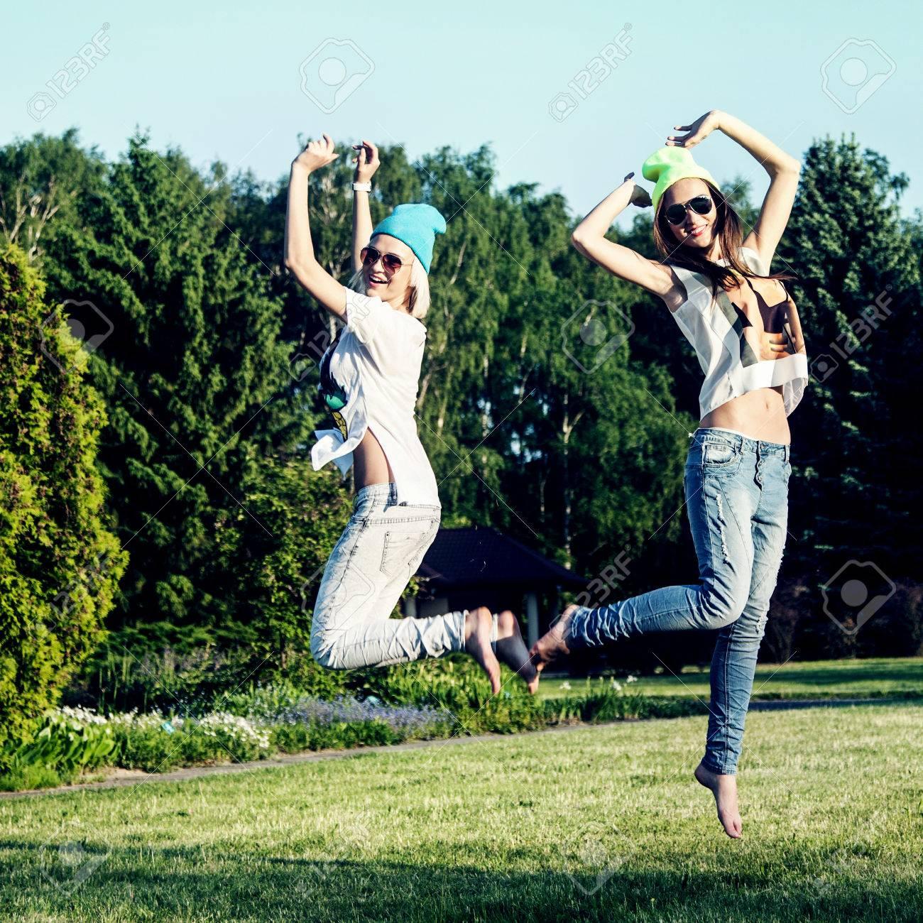 535973360668 Dos hermosas chicas jóvenes saltando en el parque, vistiendo ropa de moda.  Foto del verano. Mejores amigos.