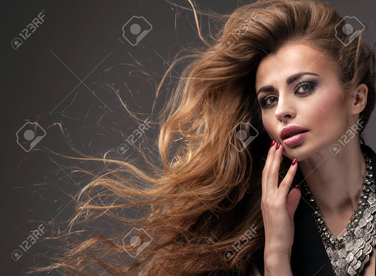 Beautiful girl with long healthy hair and glamour makeup looking at camera, wearing silver necklace