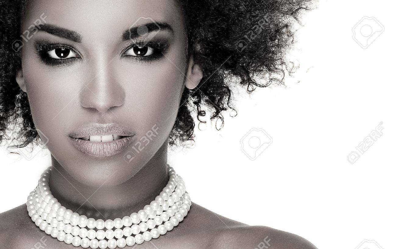 Beauty photo of young elegant african american woman with afro. Girl wearing pearls. Looking at camera. Glamour makeup. Studio shot. - 61284159
