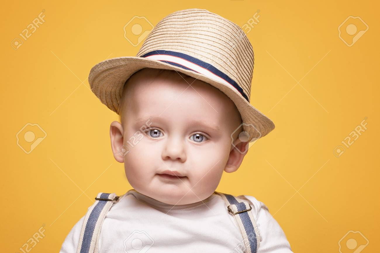 900e3630438 Cute baby boy posing in summer hat on yellow background. Adorable little  child in studio