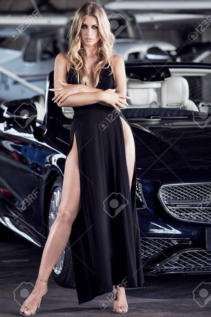Belle Femme Blonde Elegante Debout Par Une Voiture De Luxe Et Un Petit Avion Fille Portant Une Robe Noire