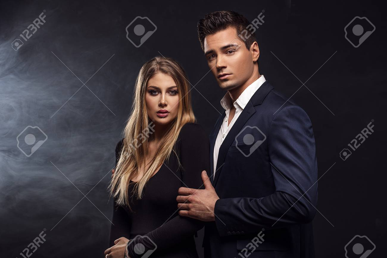 5289793f08ea5 Conceptual portrait of a young couple in elegant evening dresses. Beautiful  woman with glamour makeup