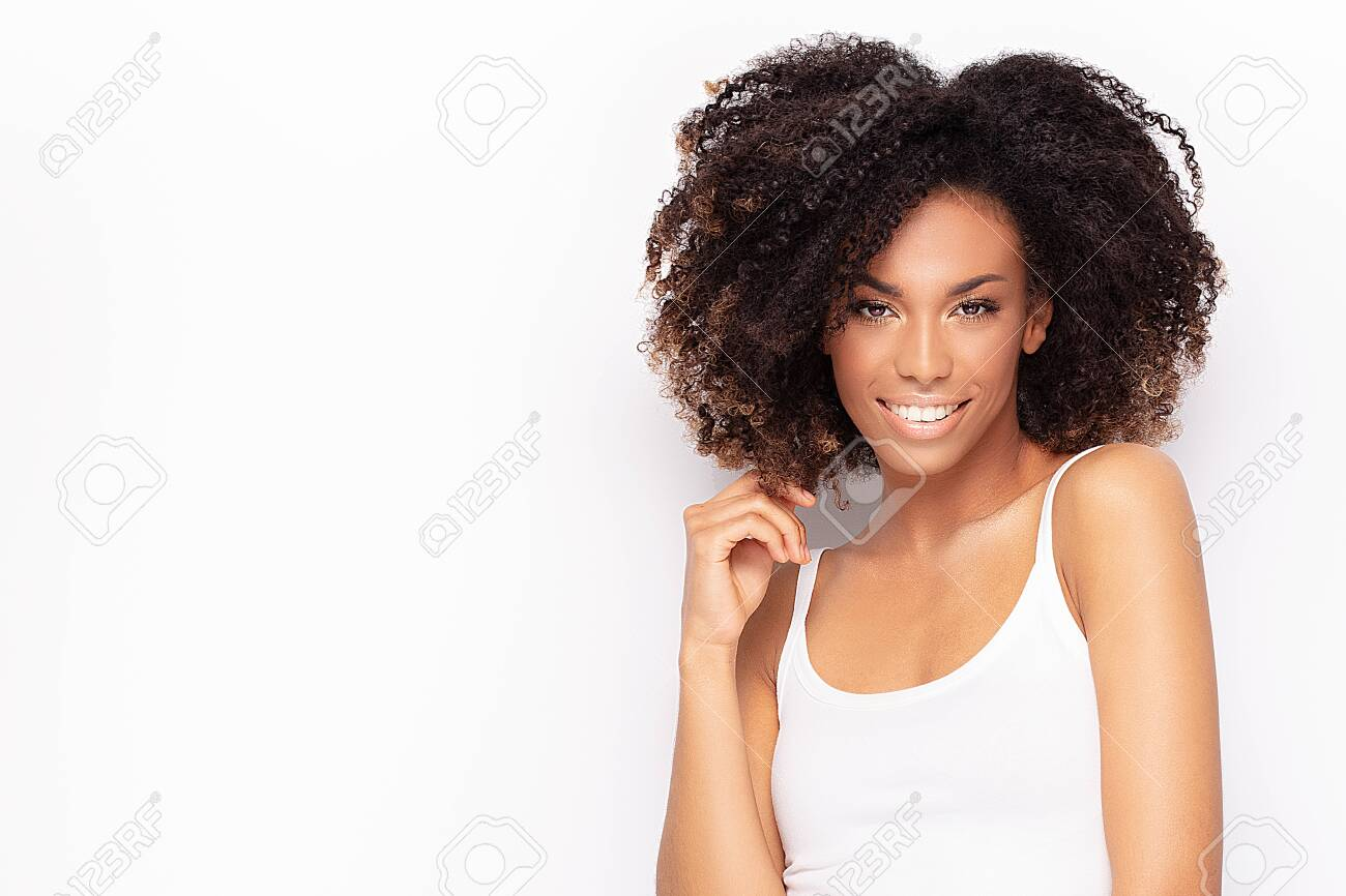 Young fashionable afro girl posing in white shirt, smiling to the camera. White studio background. - 124444740
