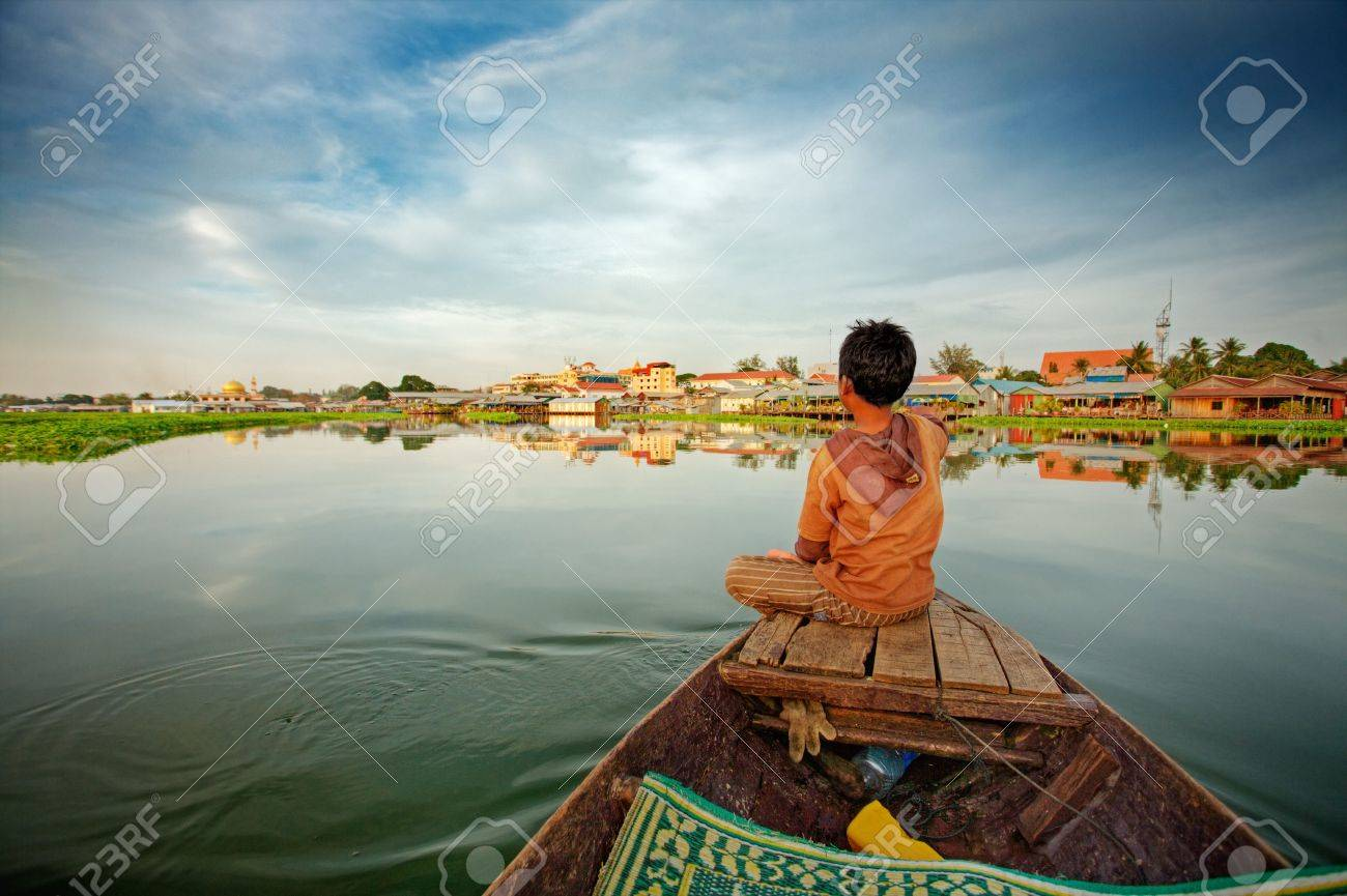 cambodian boy on prow of small boat overlooking lake stock photo
