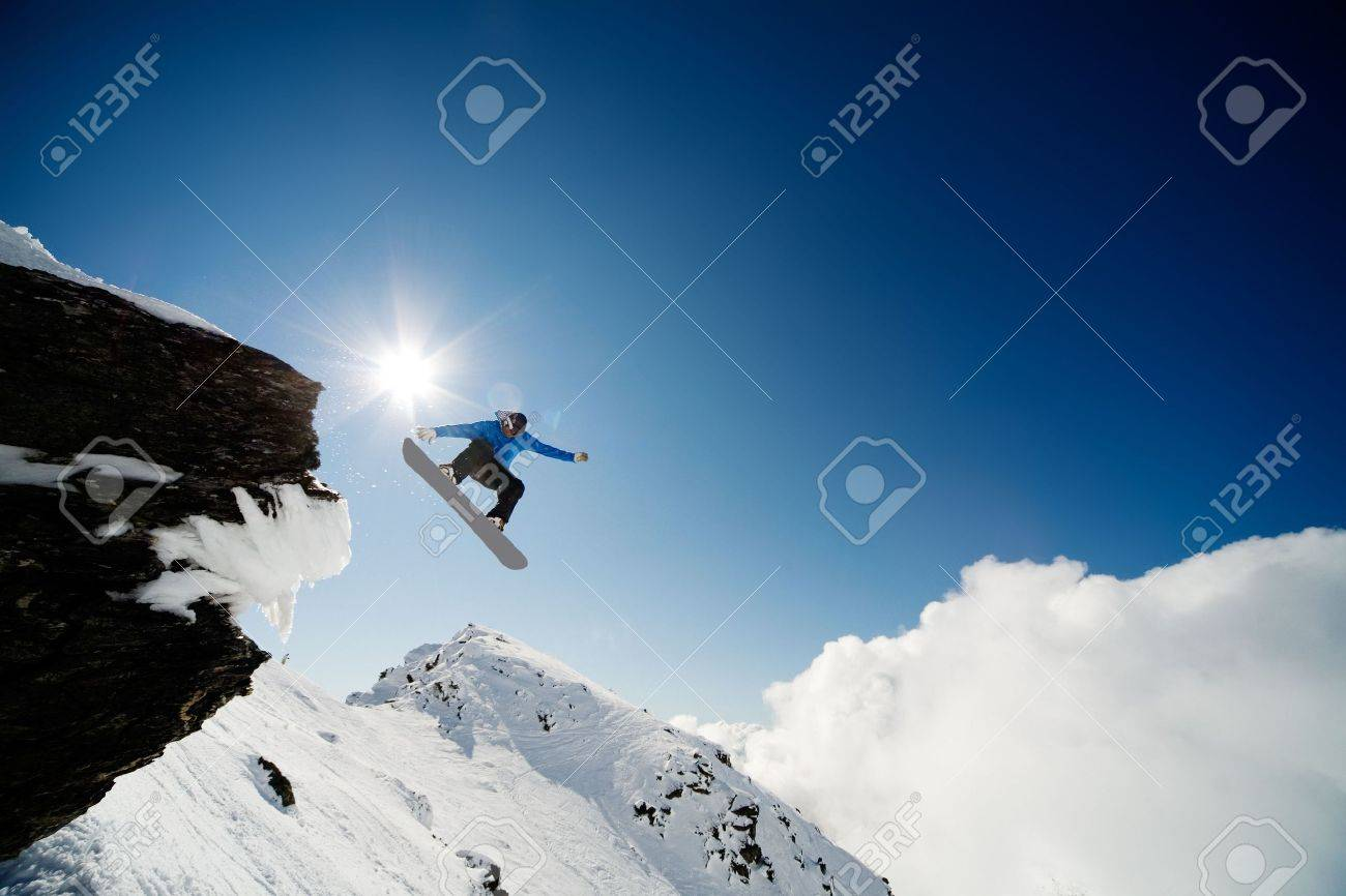 Snowboarder jumping through air after rock drop Stock Photo - 3558015