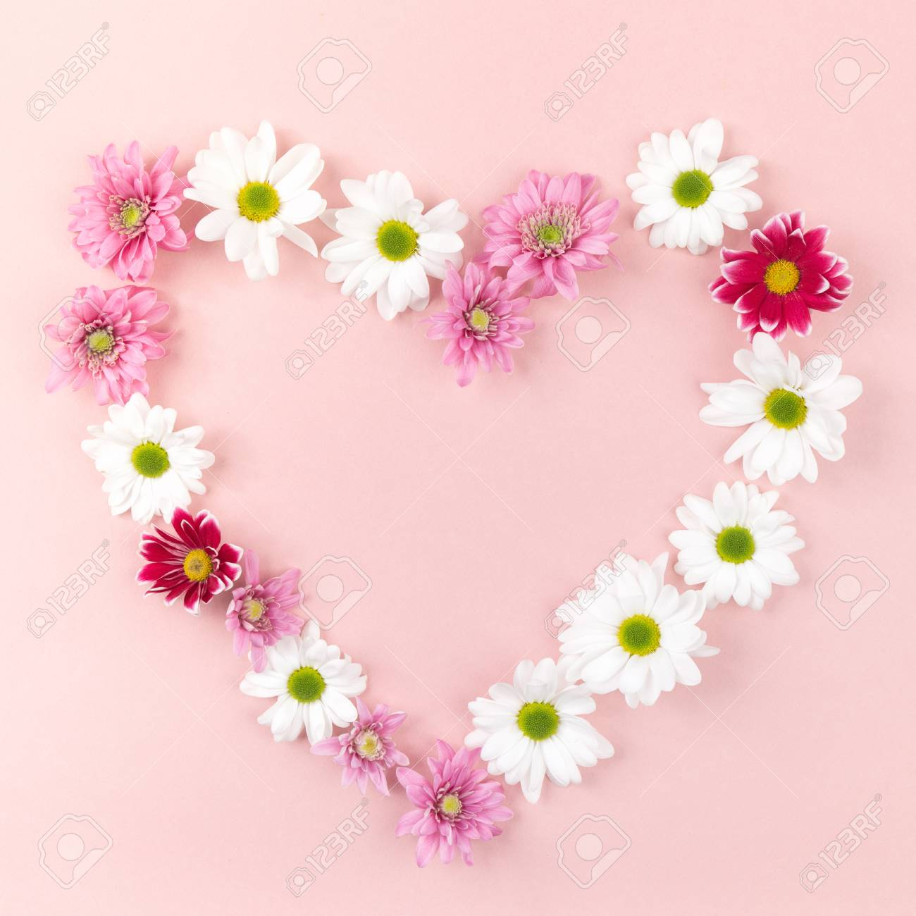 From Above Heart Made Of Different Colored Flowers On Pink