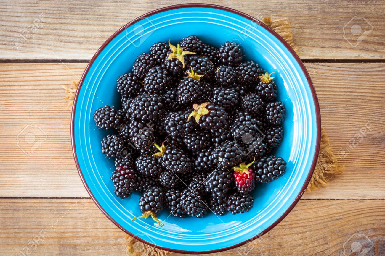 Fresh blackberries in blue ceramic bowl on wooden background in rustic style. Top view. - 61472572