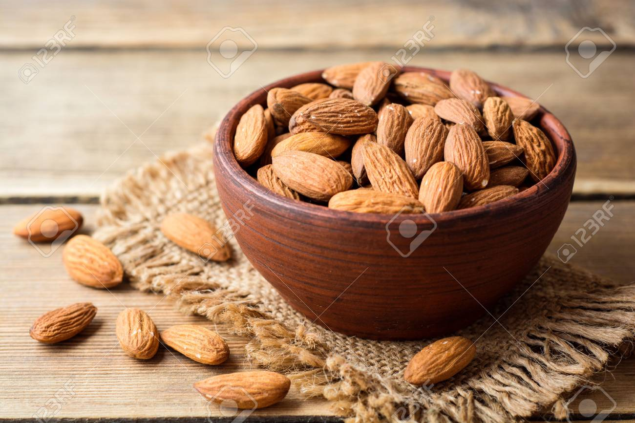 Almonds in ceramic bowl on wooden background. Selective focus. - 80896968