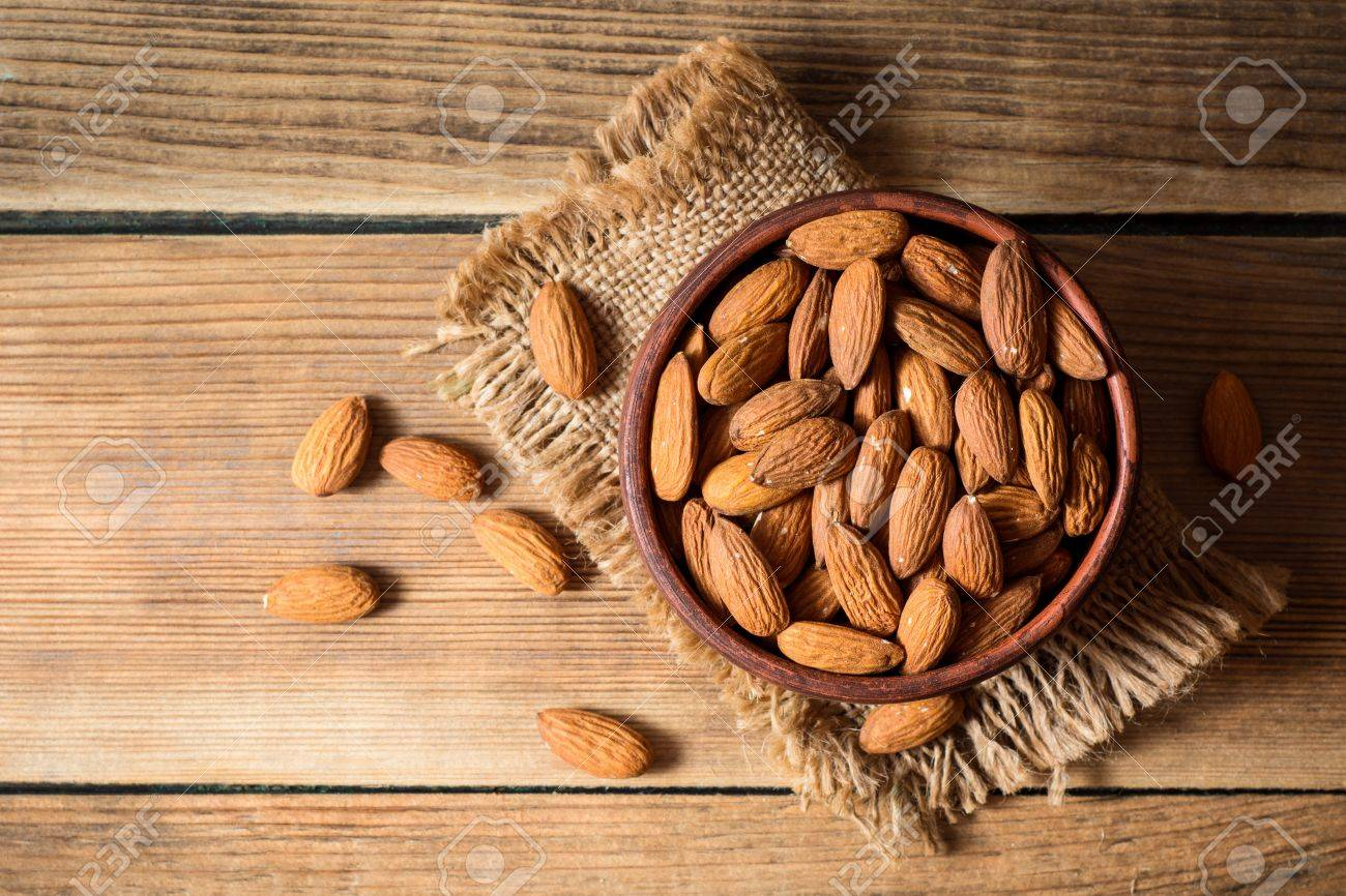 Almonds in ceramic bowl on wooden background. Top view. - 80869695