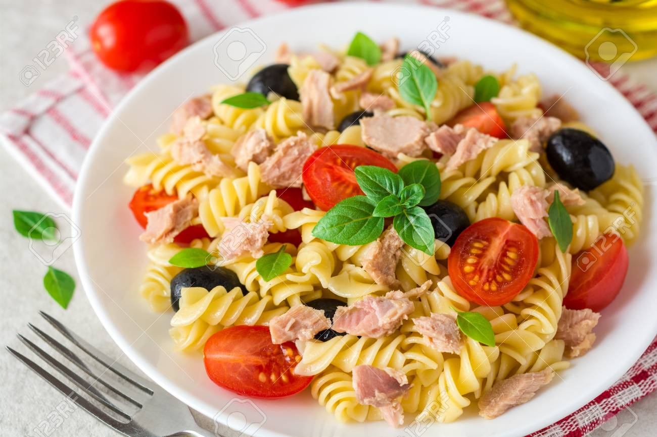 Fusilli pasta salad with tuna, tomatoes, black olives and basil on gray stone background. Selective focus. - 84623404