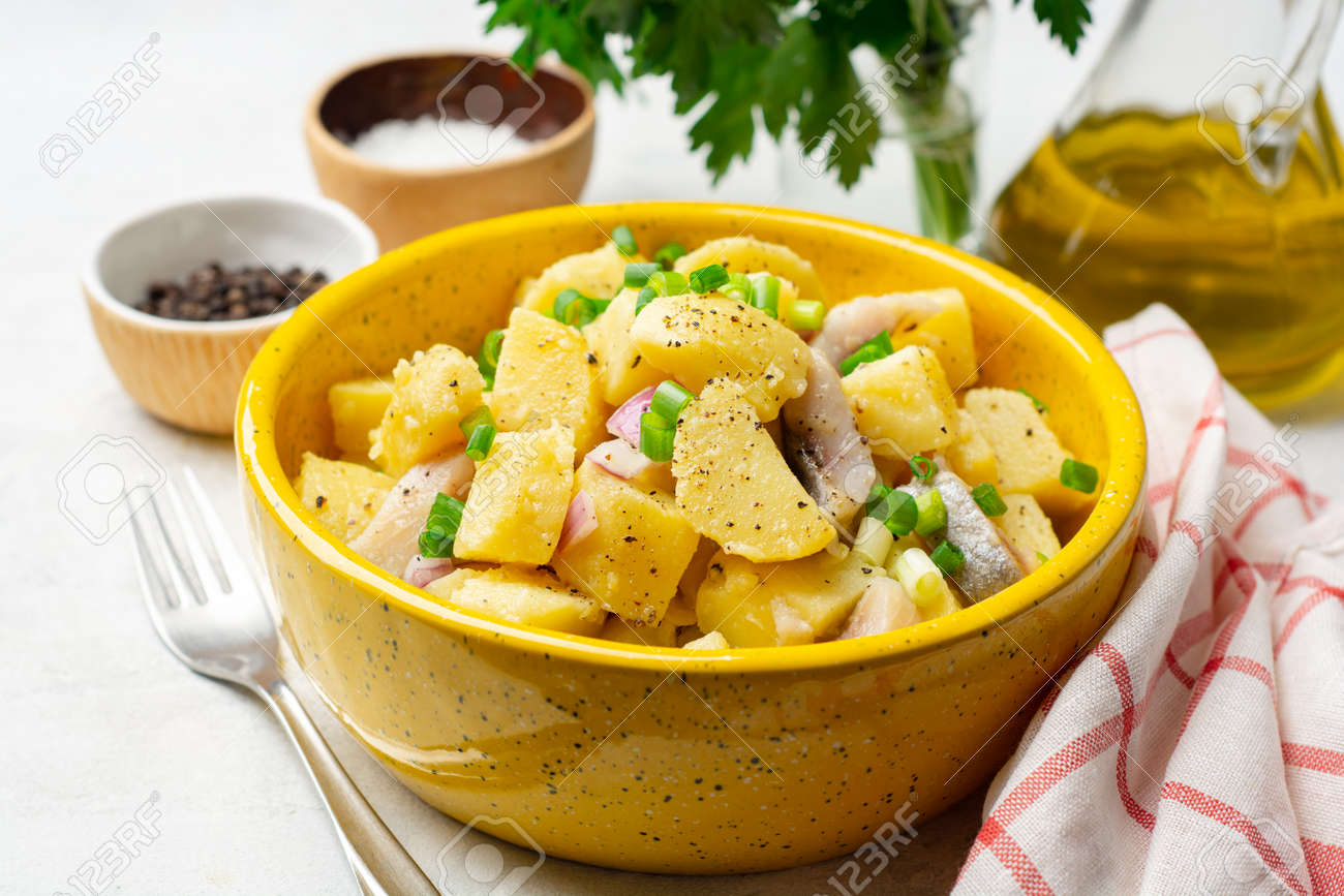 Potato salad with salted herring and onion in ceramic bowl on concrete background. Selective focus. - 164198575