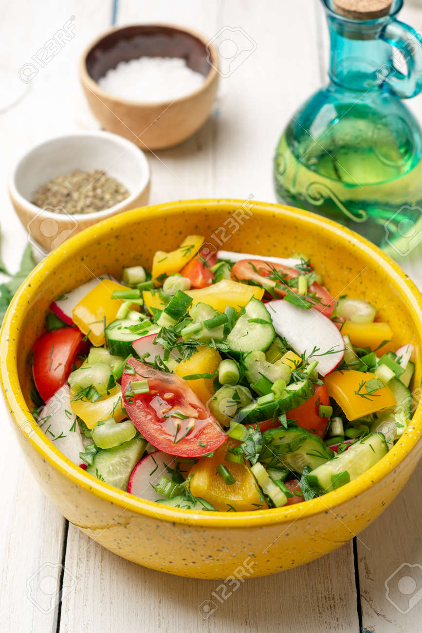 Fresh vegetables salad with radish, cucumber, bell pepper, tomato, celery and greens in ceramic bowl on white wooden rustic background. Selective focus. - 163525051