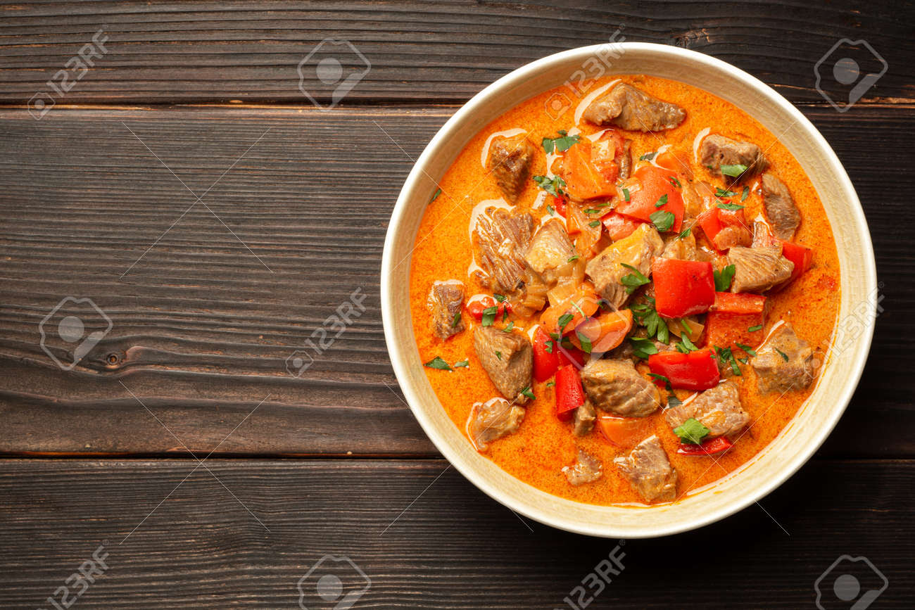Traditional hungarian paprikash with turkey, bell pepper, carrot, onion, paprika and sour cream in bowl - 169457250