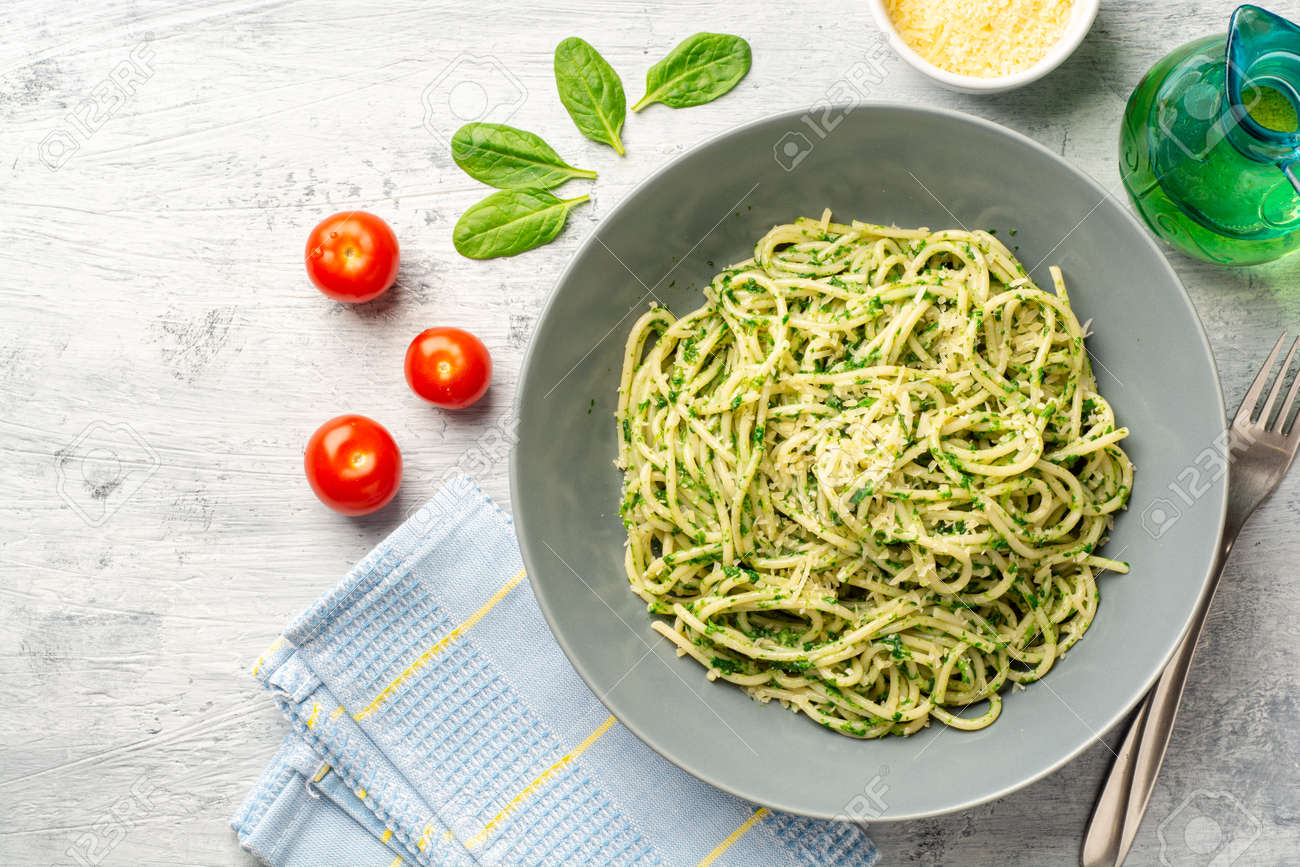 Spaghetti pasta with spinach sauce and parmesan cheese - 169457257