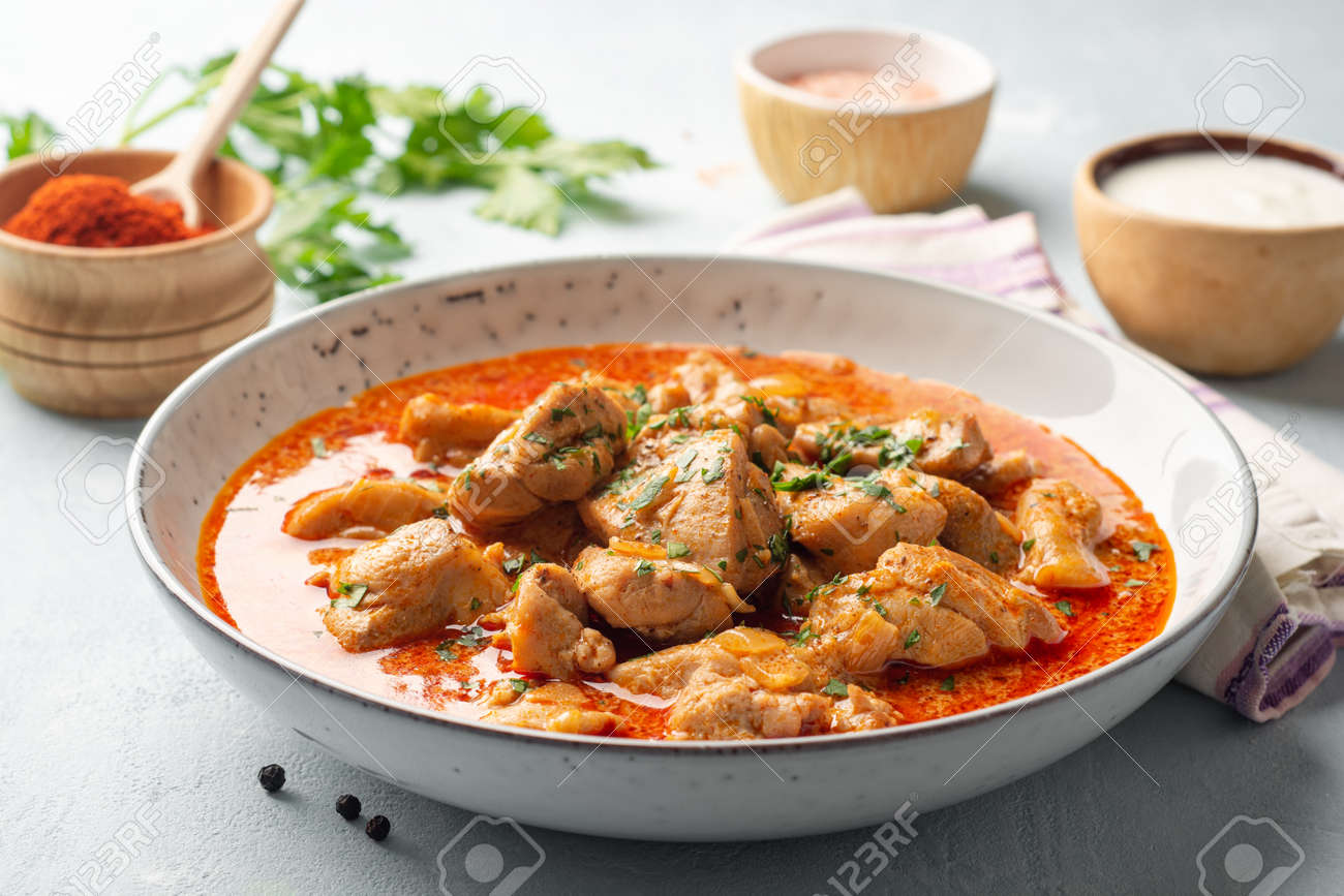 Chicken stew with paprika, onion and sour cream in plate - 169457491