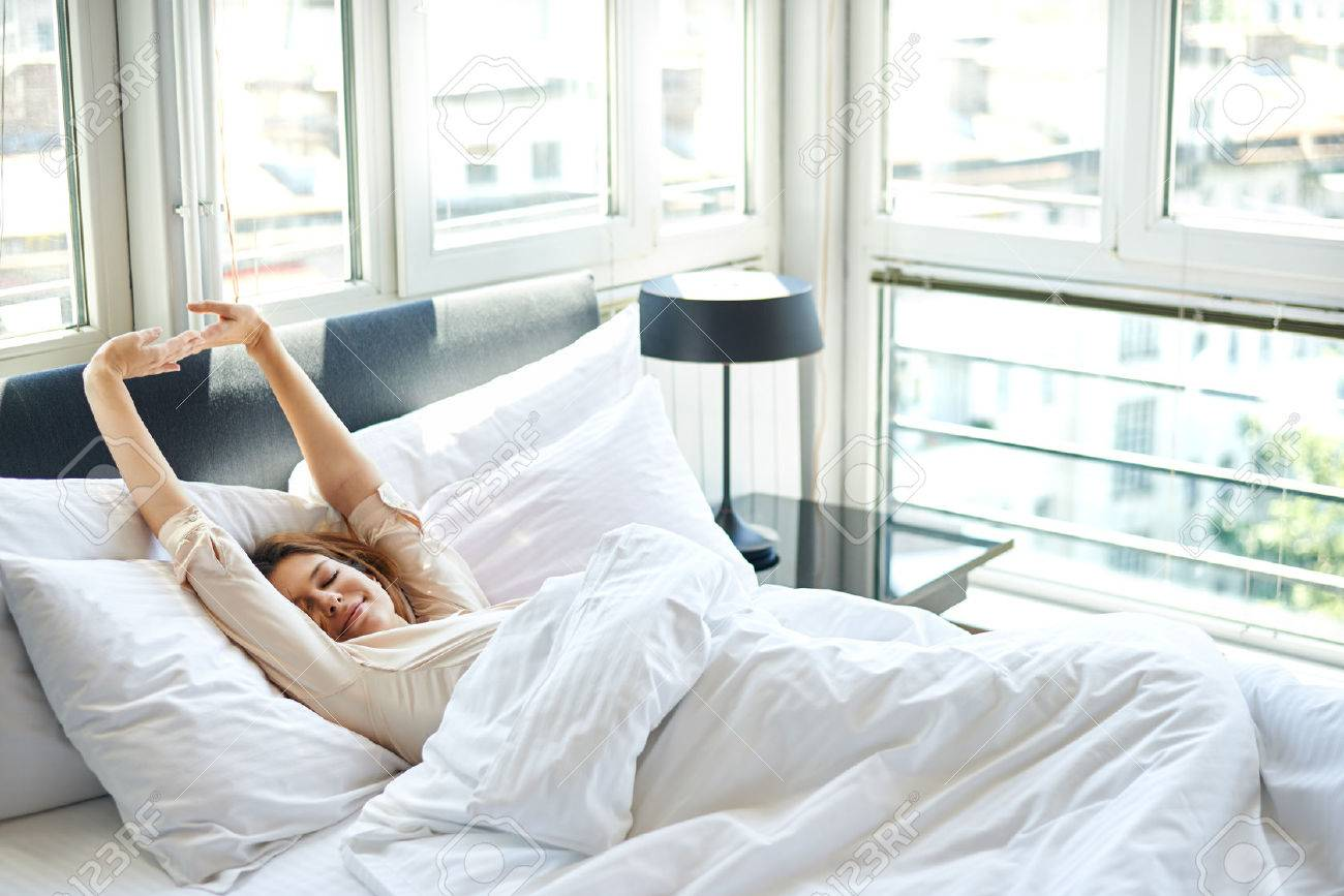 Woman stretching in bed Stock Photo - 42046412