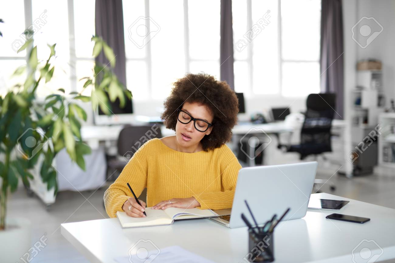 Attractive mixed race businesswoman dressed casual taking notes in notebook while sitting in modern office. On desk laptop, tablet and smart phone. - 122301512