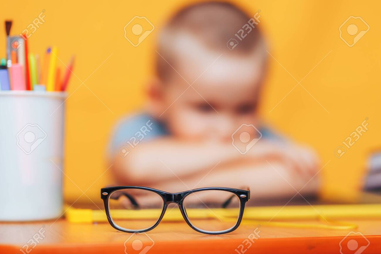 boy sitting ubfocused glasses in focus. Concept problem of ophthalmology correction of myopia. back to school. Selective focus. upset child. - 130667720