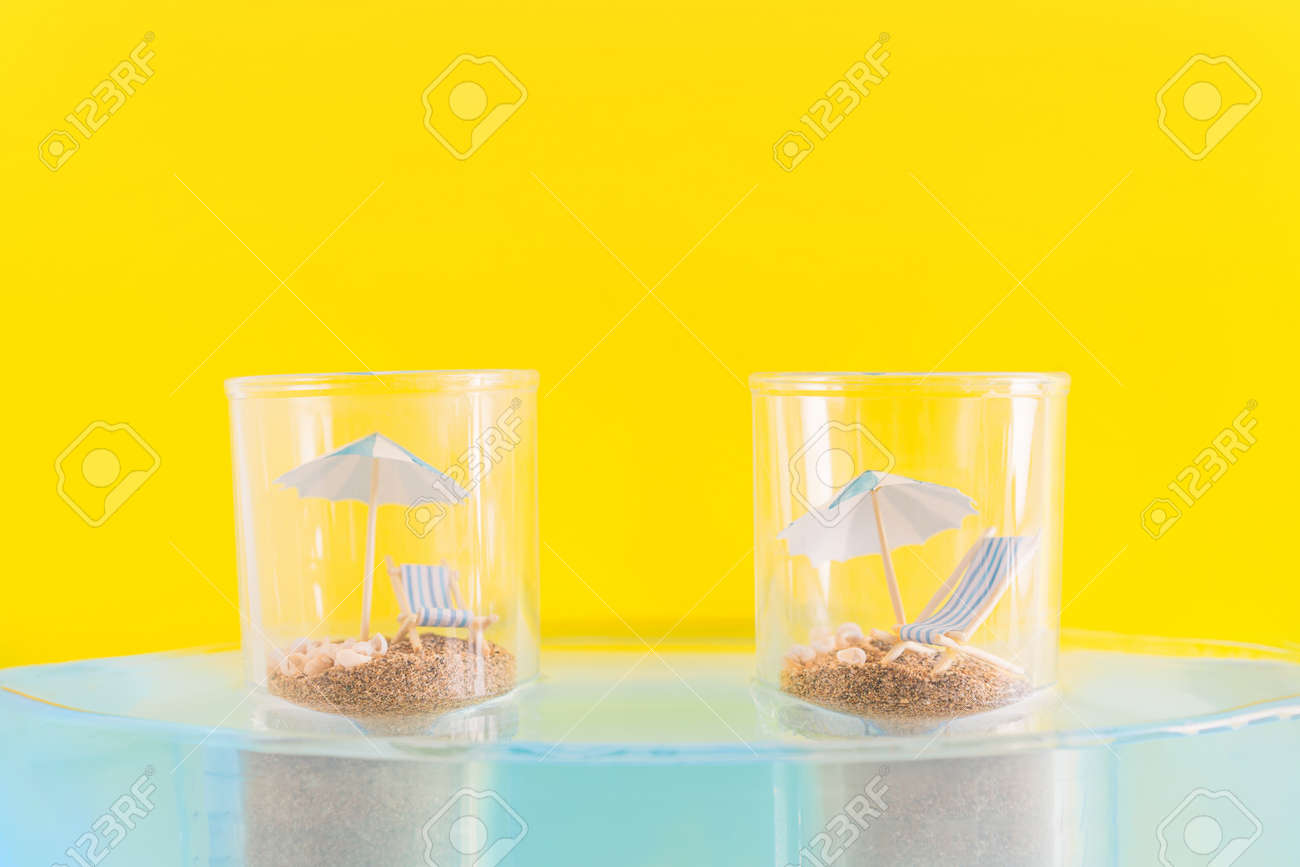 Summer vacation concept during pandemic. Social distance of people on the beach. Two glasses with sand, chaise longue and beach umbrella standing in the water. - 169603054