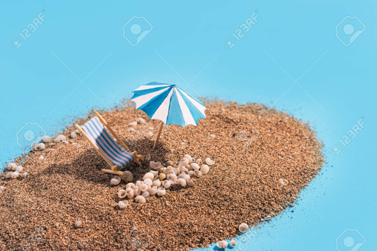 Summer vacation concept during pandemic. Slide of sand on blue background like the sea. Deck chair, umbrella and small seashells on the sand. - 169603056