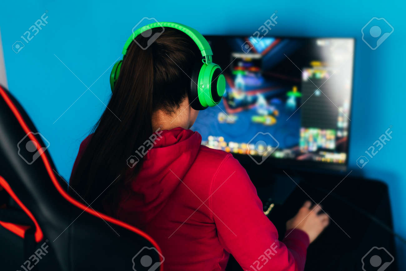 The gamer sits on a gaming chair and plays computer games. The player has green headphones on his head. - 169603059