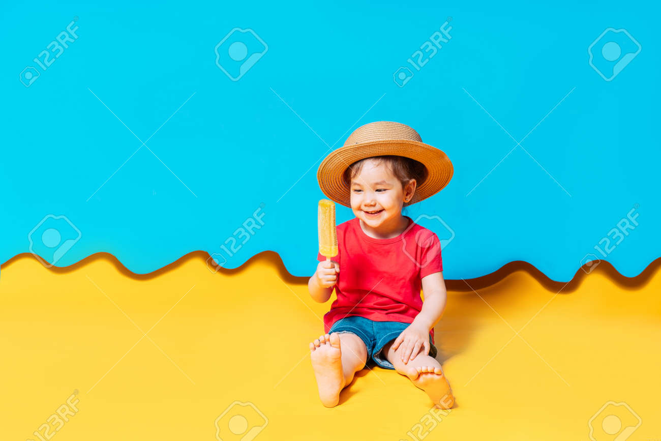 Asian girl in a straw hat licks ice cream. The blue background shows the sky, and the yellow background shows the sand. - 169603104