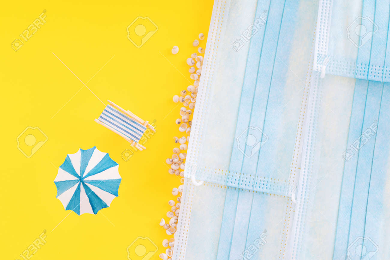 Summer vacation concept during pandemic. Medical masks are depicted as sea and yellow background as sand. Deck chair, umbrella and small seashells standing on yellow background. - 169603127