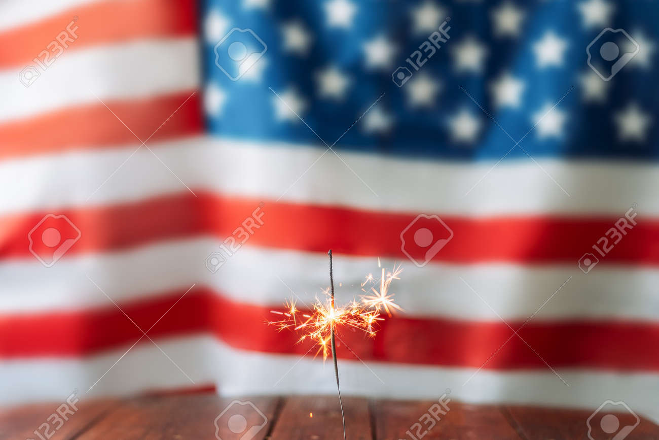 Bengal fire on wooden table in front of the blurred american flag background. - 169694070