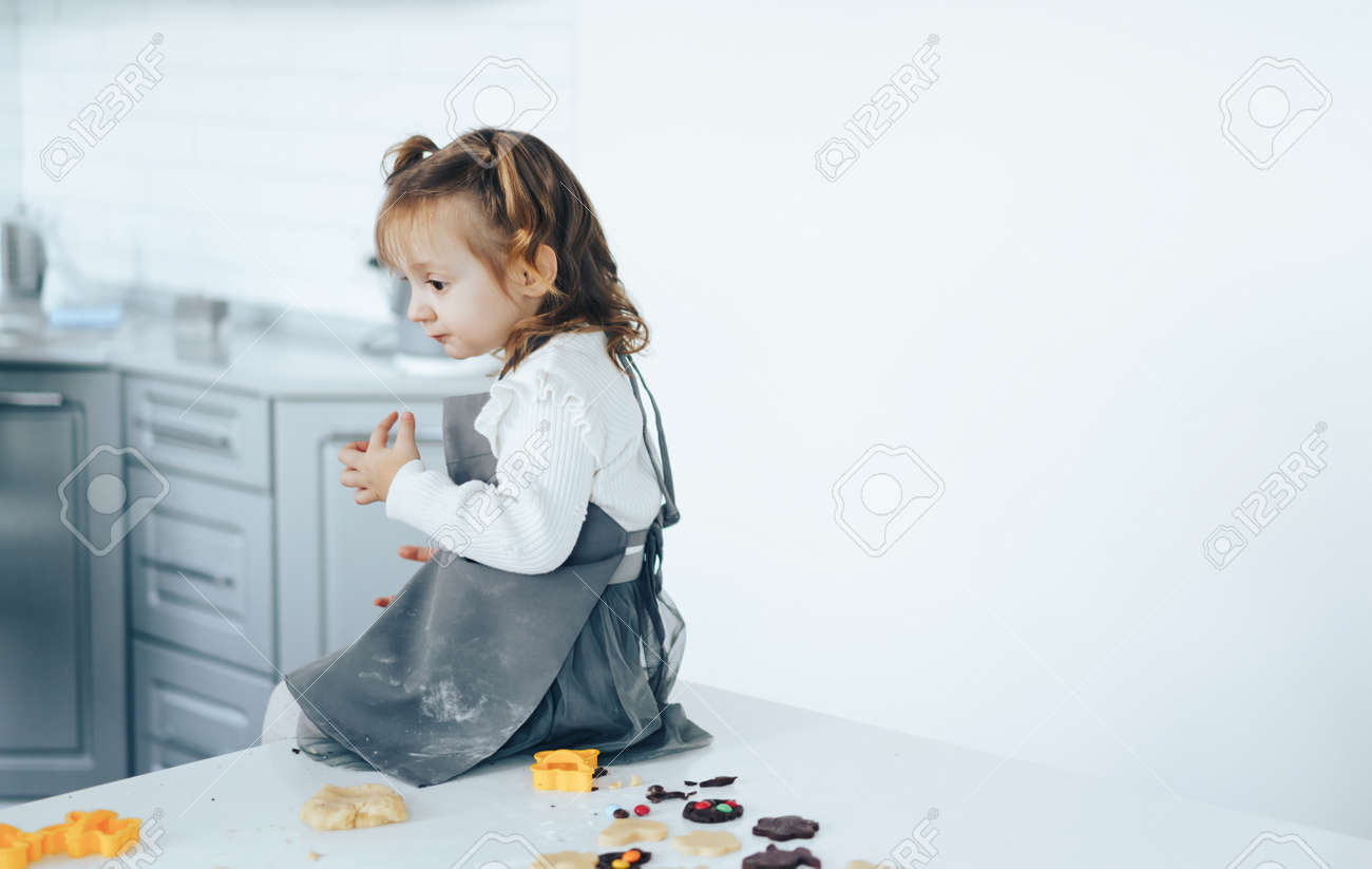 Little girl cooking sweet cookies, sitting on table. - 169694078