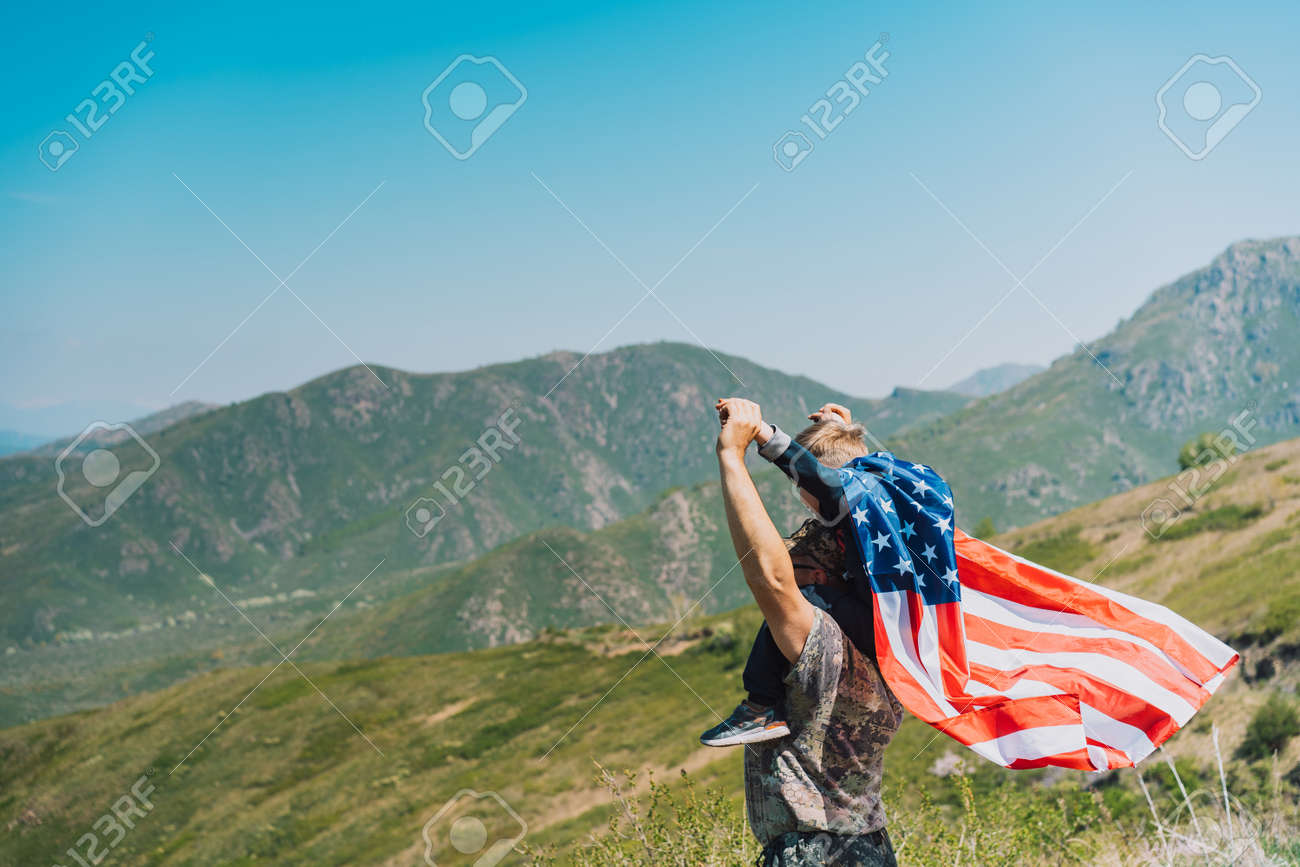 Man and child celebrate fourth of july with american flag in nature. - 169694085