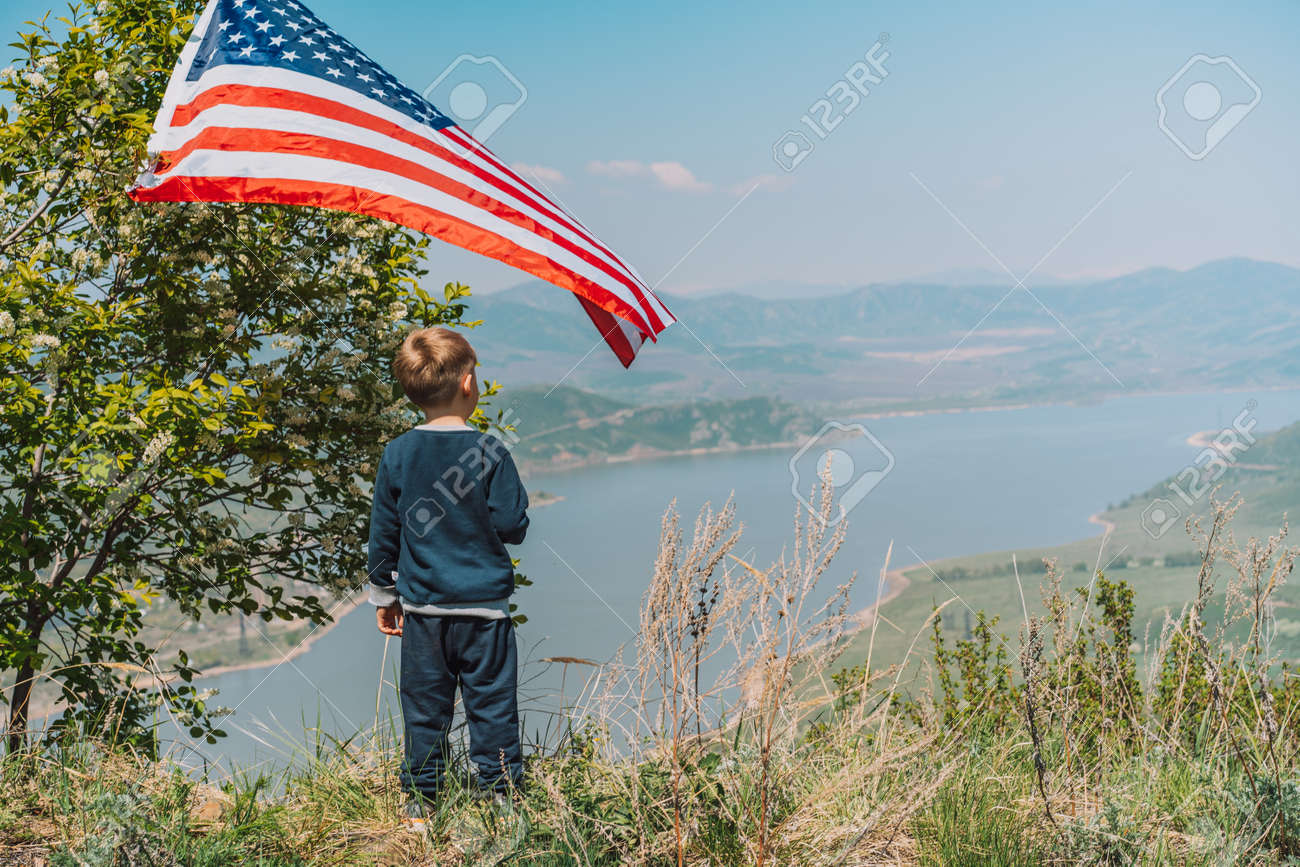 Little boy with American flag looks into the distance at nature. 4th of july - 169694092
