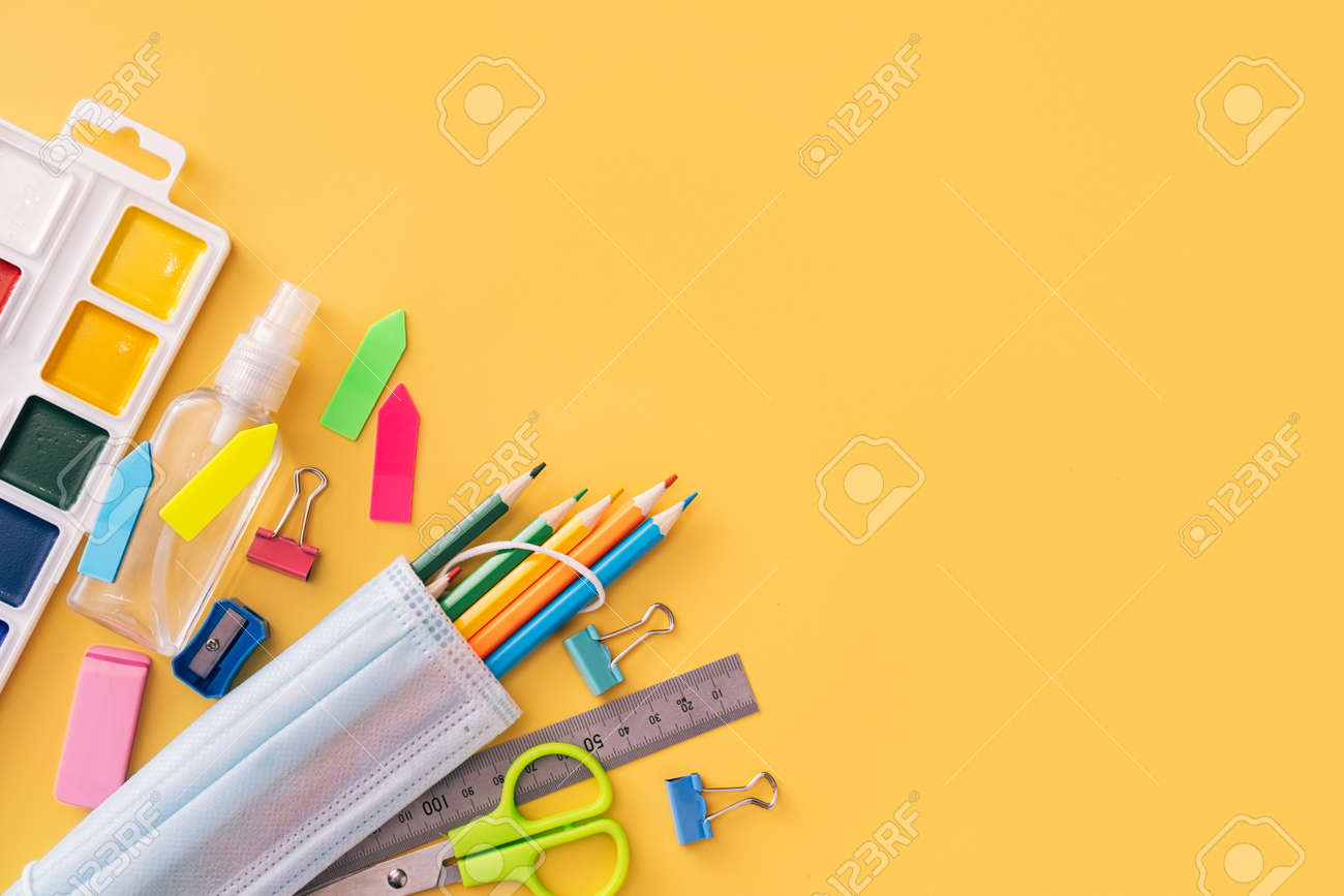 School supplies with paints, medical mask and antiseptic on yellow background. - 169694337