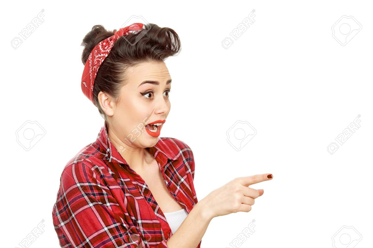Portrait of a beautiful pinup girl in a plaid shirt wearing a red bandana  in her hair looking surprised shouting and pointing at the copyspace  isolated b9d1c25acf4