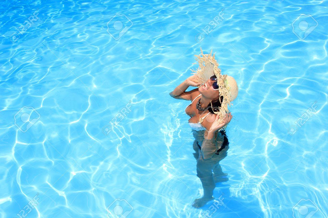 Young woman with straw hat enjoying a swimming pool Stock Photo - 16508405