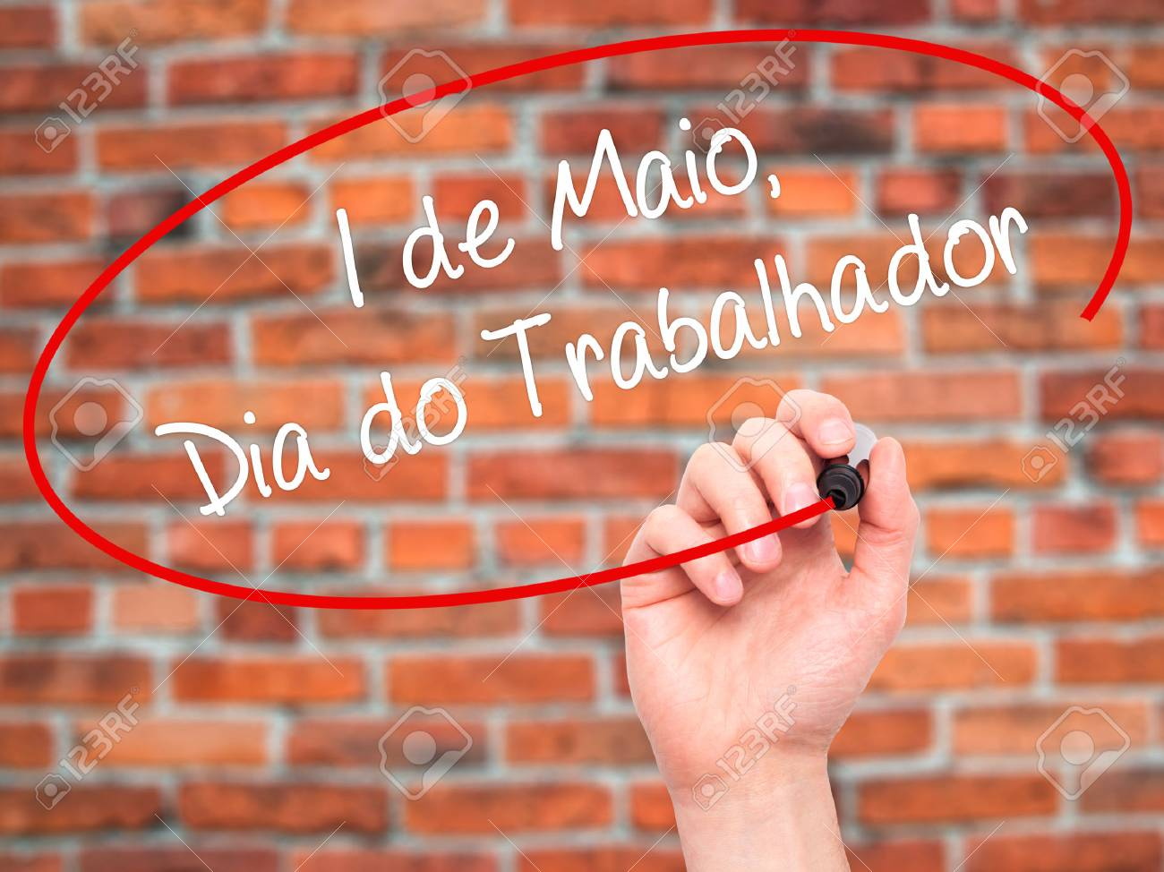 Man Hand writing 1 de Maio, Dia do Trabalhador (In Portuguese: 1 May, Labor Day) with black marker on visual screen. Isolated on bricks. Business, technology, internet concept. Stock Photo - 52239624