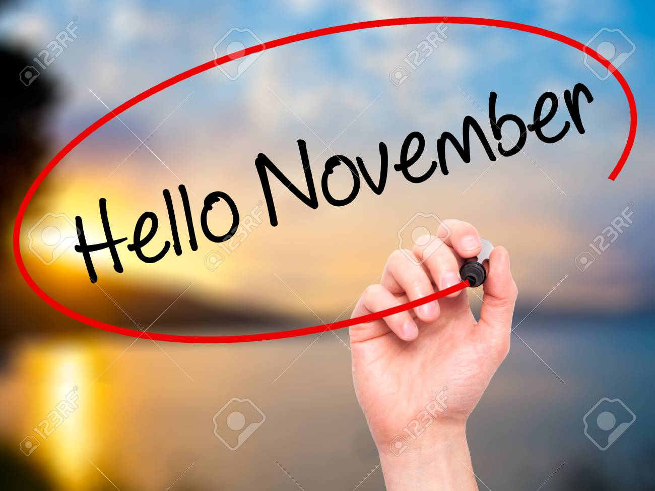 Man Hand Writing Hello November With Black Marker On Visual Screen.  Isolated On Nature.