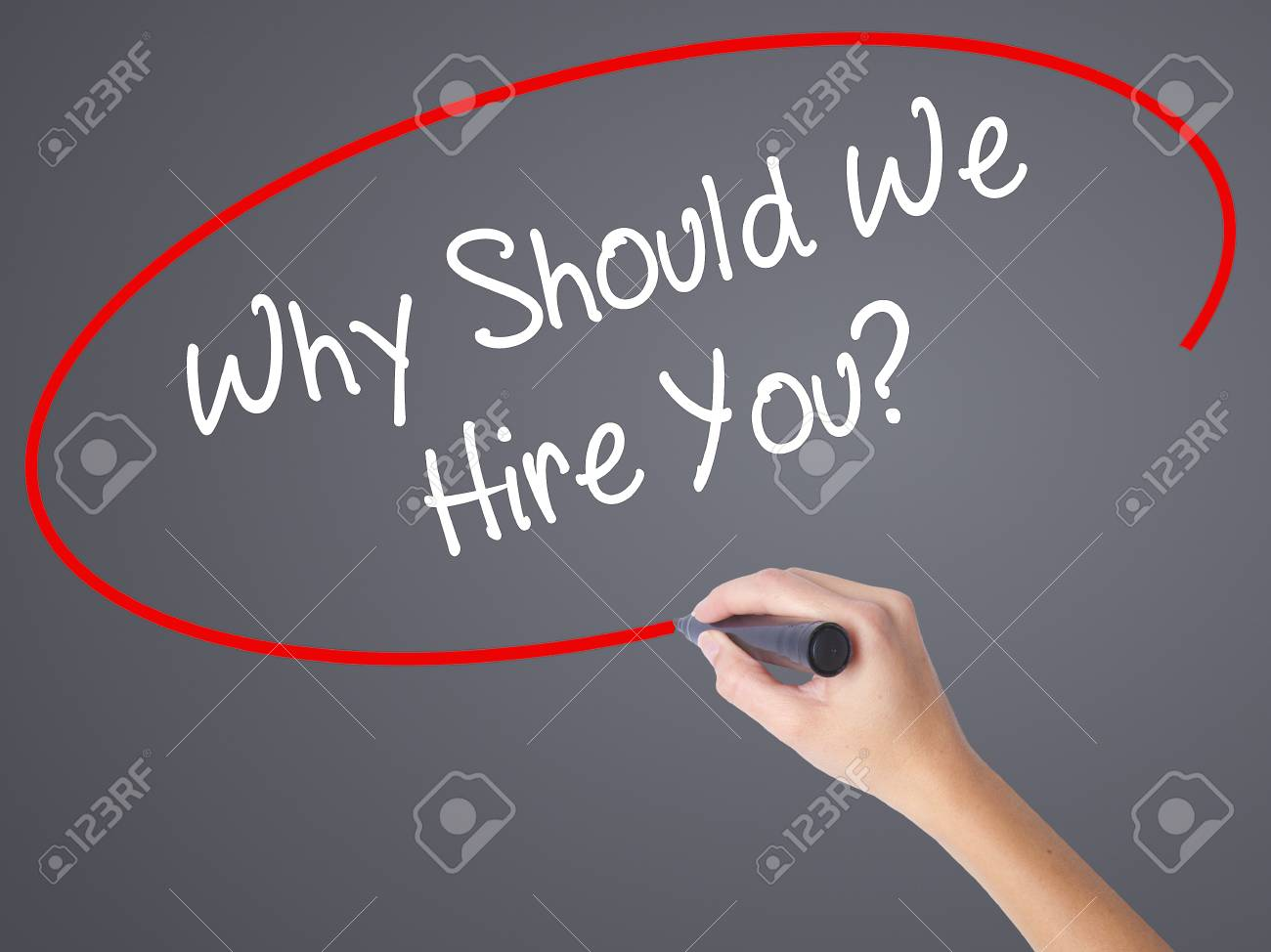 woman hand writing why should we hire you with black marker stock