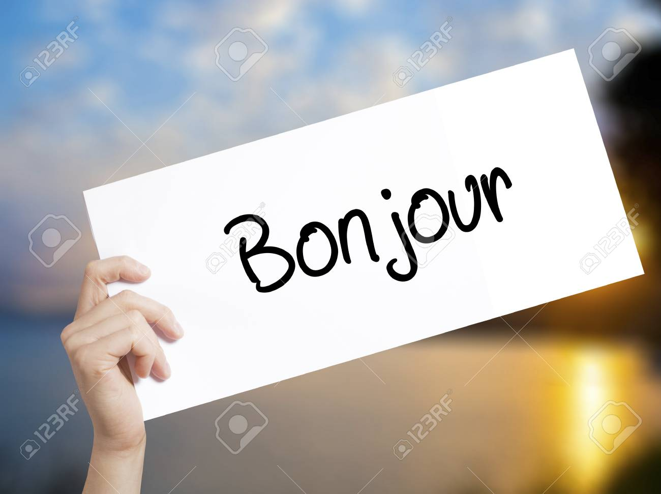 Bonjour Bom Dia Em Francês Cadastre Se Em Papel Branco Mão De Homem Segurando Papel Com Texto Isolado No Fundo Por Do Sol Conceito De Negócios