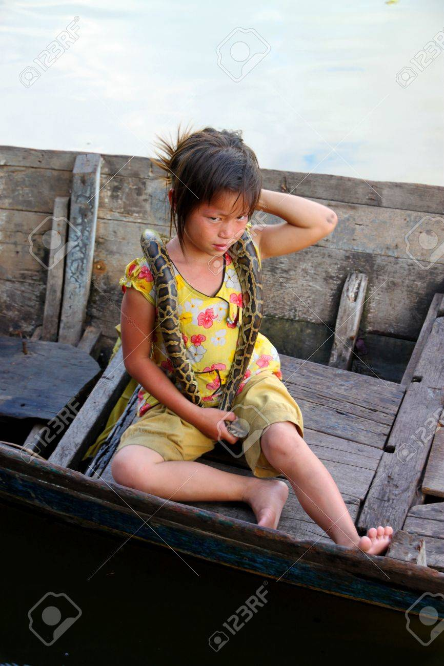 SIEMREAP, KHMER REPUBLIC - NOVEMBER 5 : The unidentified Khmer girl is sitting on boat and playing with  python show to the tourists on November 5, 2011 at Tonle Sap Lake, Siemreap, Khmer Republic. Stock Photo - 11542745