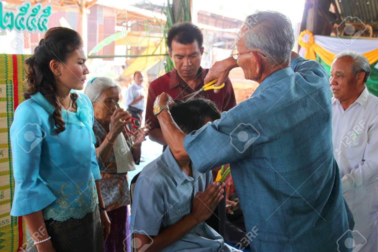 YANGSRISURAT, MAHASARAKHAM - MARCH 22 : Unidentified close relative is cutting man hair in ordination ceremony on March 22, 2012 at Wat Nongbuasantu, Yangsrisurat, Mahasarakham, Thailand. Stock Photo - 13491310