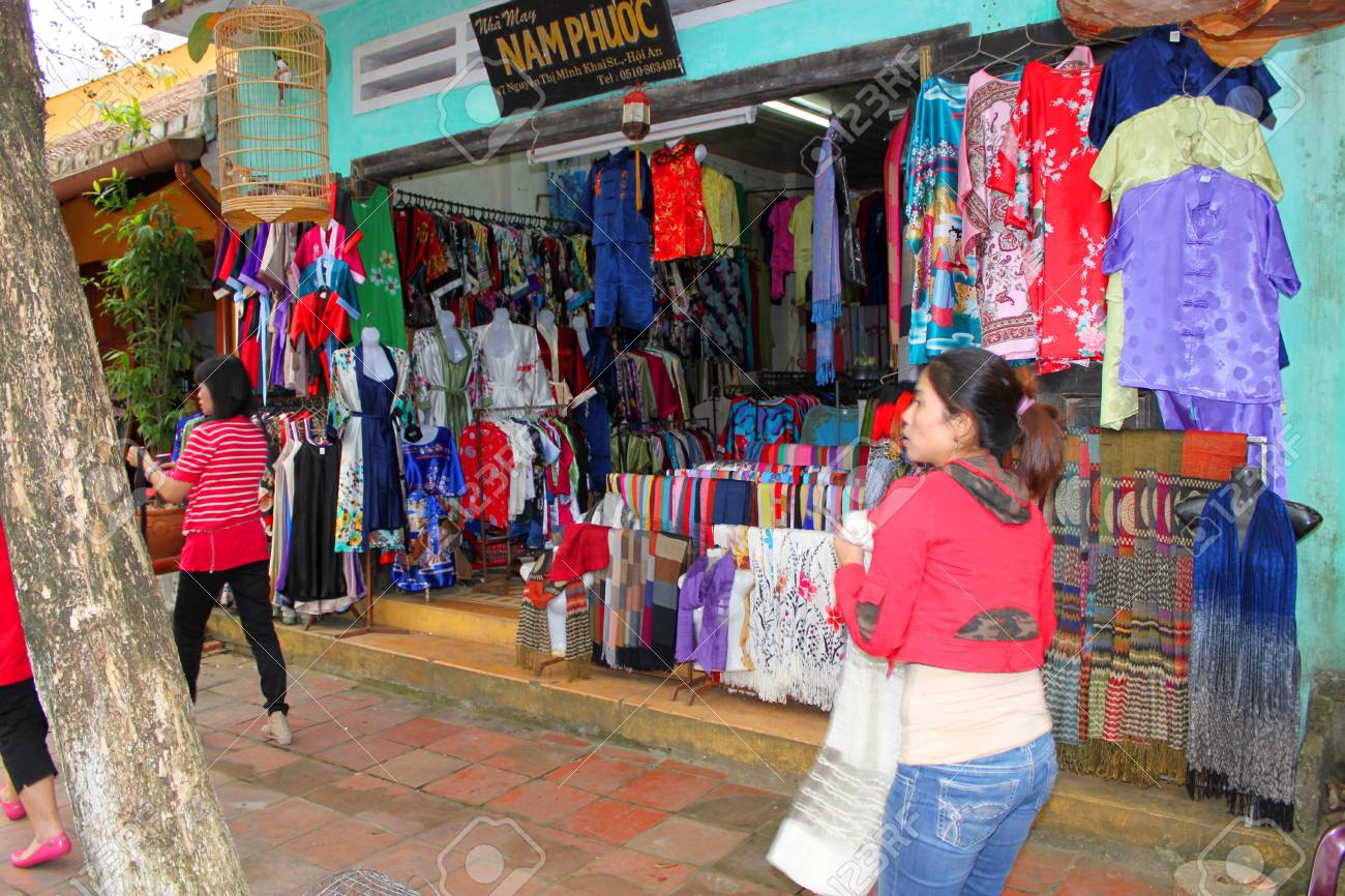 HOI AN, CENTRAL VIETNAM - DECEMBER 8 : Unidentified tourists are shopping on walking street and cycling of world heritage old town on December 8, 2012 at Hoi An, Vietnam. So wonderful with old aged traditionally kept cultural activities, habits and custom Stock Photo - 16994767