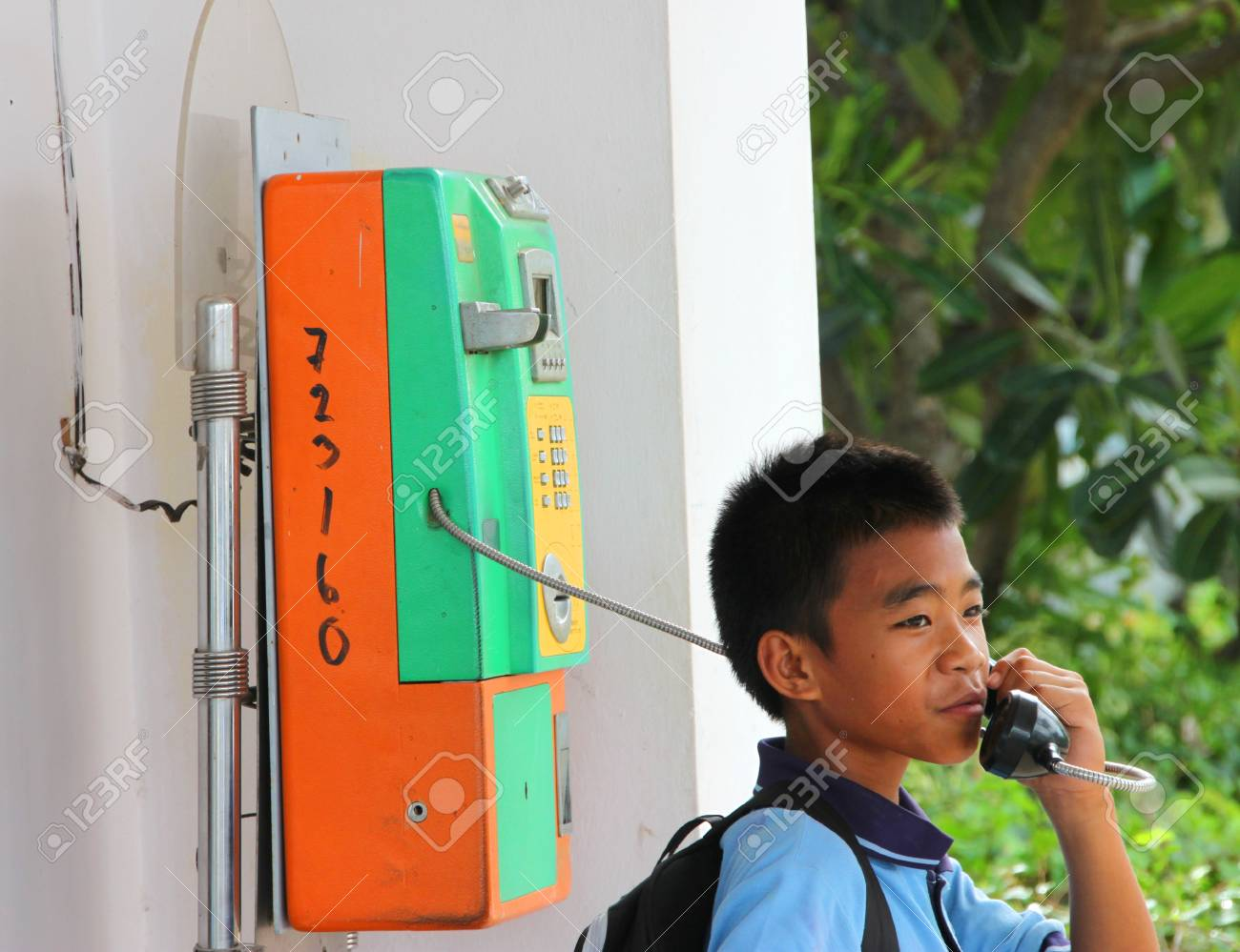 MUANG, MAHASARAKHAM - JUNE 8 : Unidentified boy is calling to somebody by telephone on June 8, 2012 at city hall of Muang, Mahasarakham, Thailand. Stock Photo - 17063343