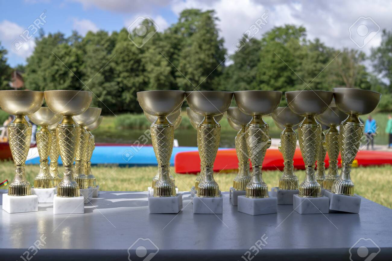 Table set with a lot of sporting trophies outdoors in the shade