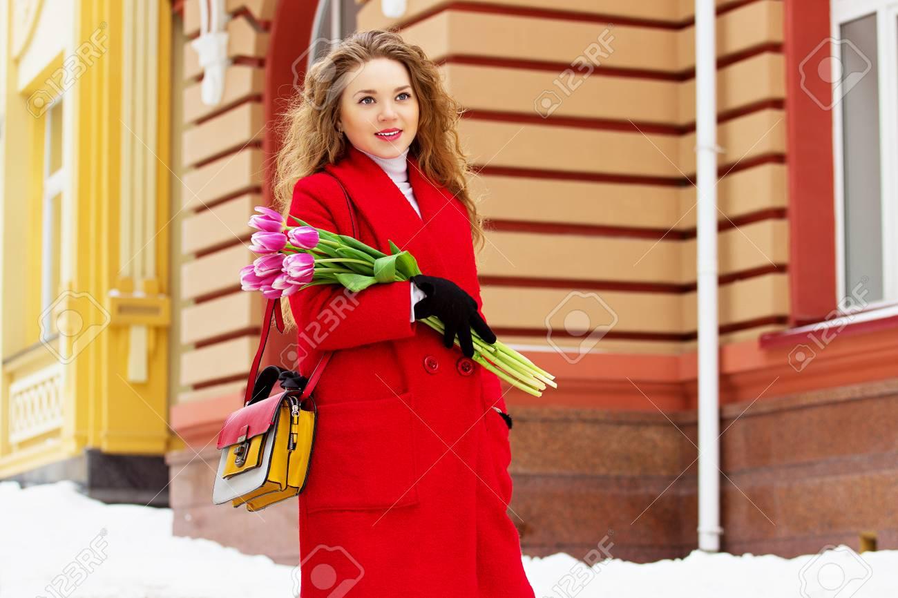 bas prix f9341 d84bd Belle jeune et élégante fille blonde en manteau rouge tenant des fleurs.  Accessoires pour femmes. Printemps.