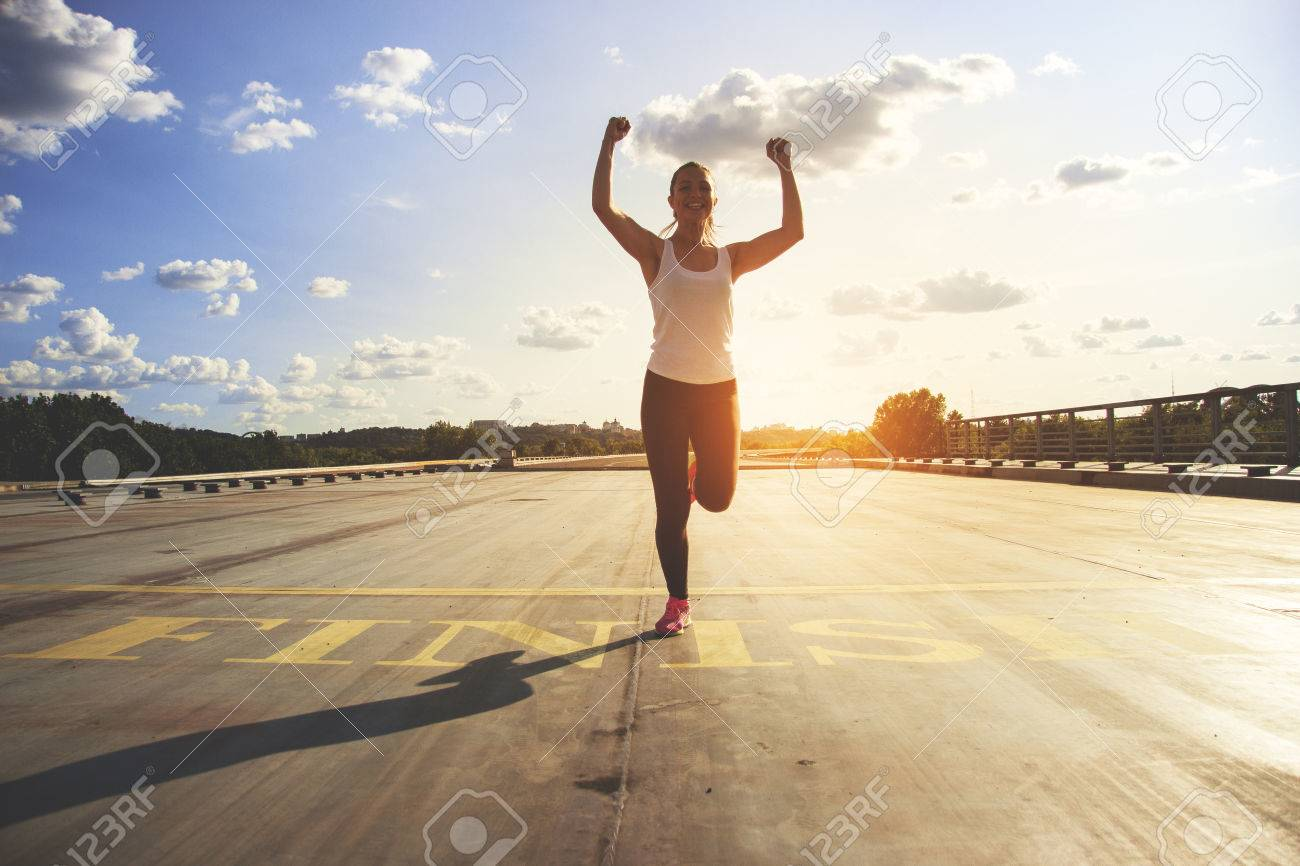 Winner as style of life. Horizontal shot of young beautiful woman in sports clothing keeping arms raised and smiling while passing finish line during jogging. Evening sunlight on background. - 83547835