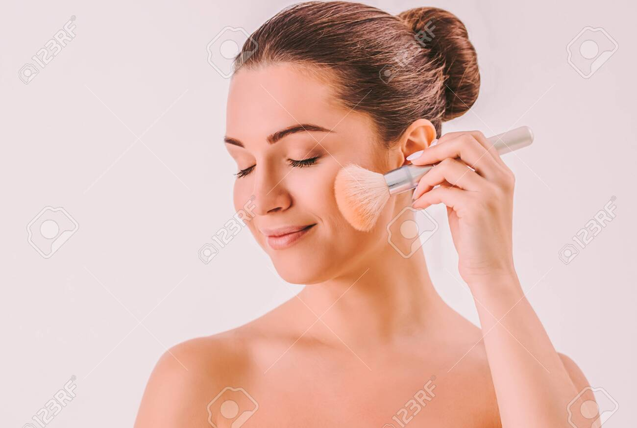 Young Beautiful Woman Applying Makeup On Face And Smiling Attractive Stock Photo Picture And Royalty Free Image Image 145293537