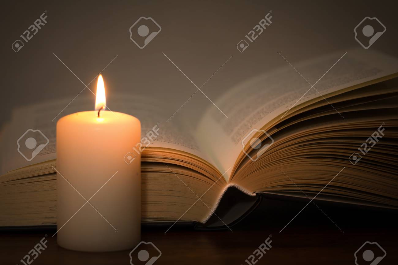 book and burning candle - 79638063