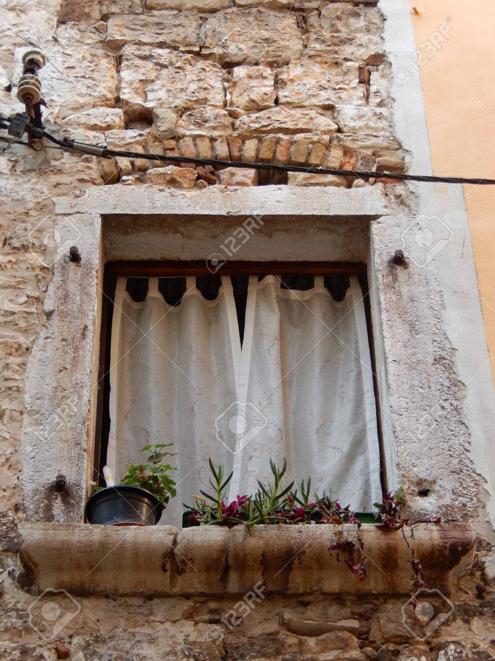 Old window with white curtains and flowers on a stone facade stock old window with white curtains and flowers on a stone facade in rovinj croatia mightylinksfo