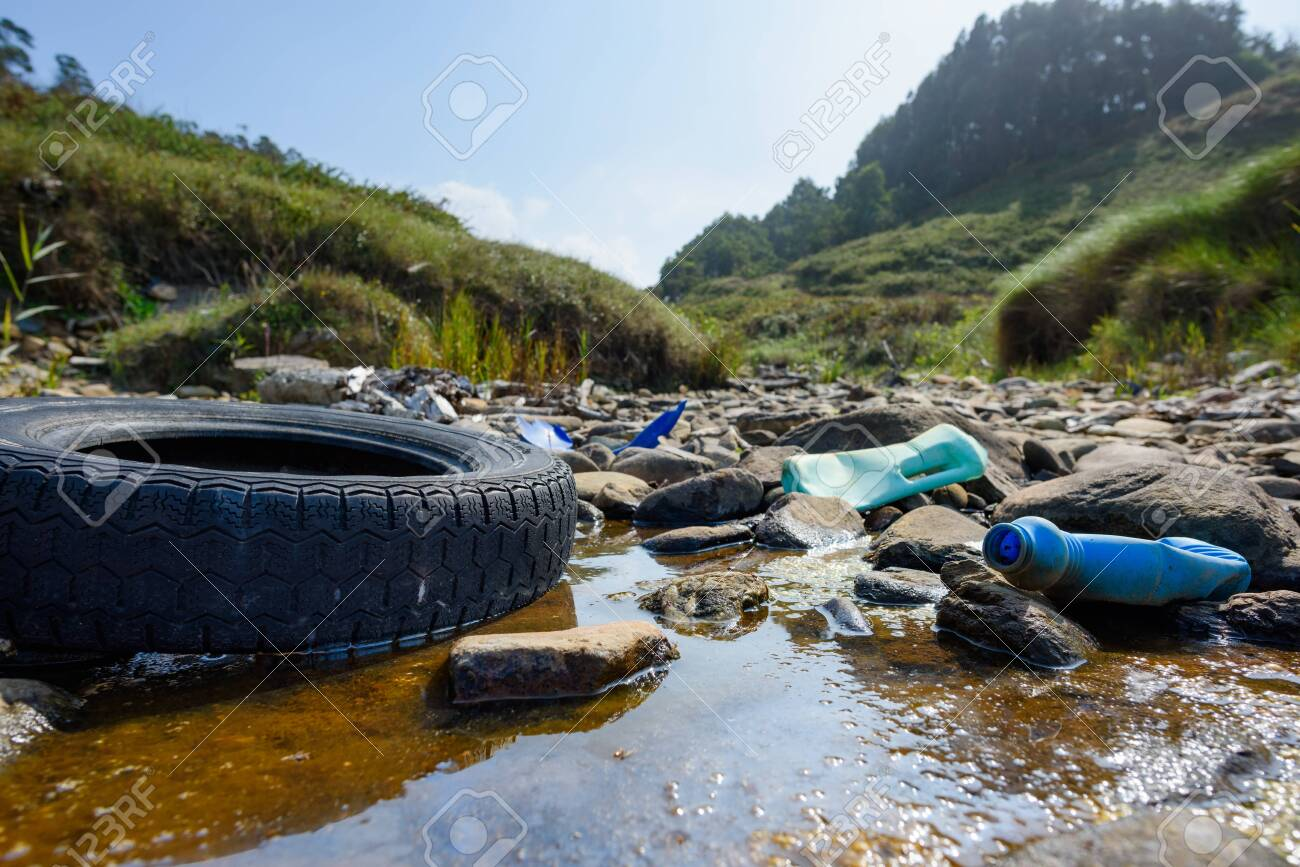 Earth plastics pollution global enviroment emergency. Old car tire in dirty water with plastic bottles and trash. - 131313552